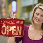 New Business Owner holding an open for business sign