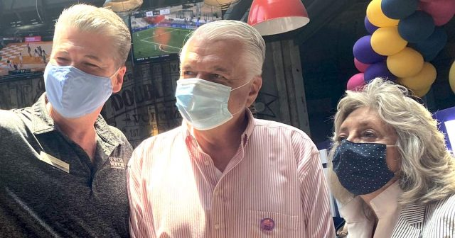 Sisolak and Titus pretending to wear masks